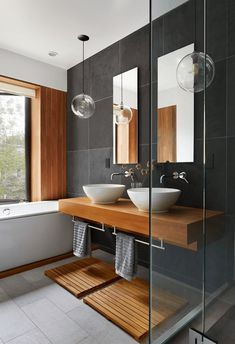 modern bathroom with dark bronze accent wall warm wood accents gray floor tile white vessel sinks sherwin williams sealskin dark bronze dark brown blackish-brown brownish-black warm black