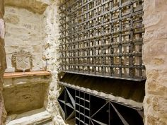 Stone-lined wine cellar with wrought iron racks...