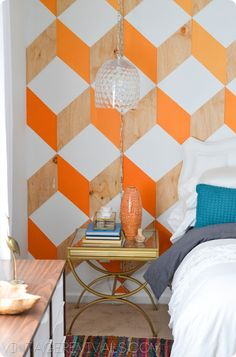 Vintage Revivals - couldn't find a tutorial on this wall, but it looks like a bunch of thin wooden parallellograms - some painted, some not, on a white wall.  There is an  ombre affect across the wall - darkest orange on left and ligher yellowy-orange on right.
