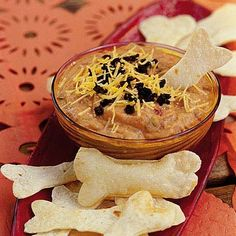 Goblin Dip with Bone Crackers Turn Tex-Mex bean dip into a Halloween specialty by serving it with bone-shaped crackers.