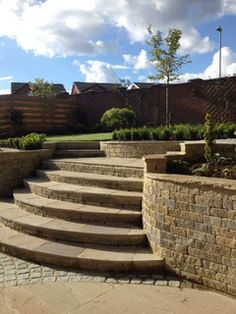 Curved garden stone steps and stone curved walls with stone paving and granite sets by Paperbark Garden Design for Yorkshire garden.