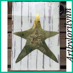 Glamorous starfish, adorned in gold chunky jewel and peacock feathers . Done on white distressed floor board. Wish upon a star!