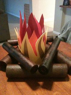 Campfire made from spray painted swim noodles then hot glued together. Flames are made from foam sheets cut flat into flames, then rolled into a tube and hot glued to stay in tube shape giving it a random flame look.