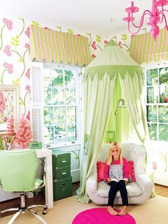 This cheery girl's bedroom in Charlotte, North Carolina, was inspired by its graphic floral wallpaper.  The pink-and-green color scheme is found in the bedding and fabrics and punctuated with a hot pink chandelier and green desk accessories. Awning-like valances and a canopied reading hideaway keep the room youthful and dreamy. (Photo: Alexandra Rowley)