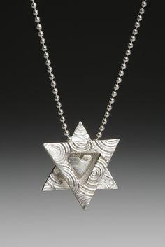 Modern and petite Jewish Star Necklace by Rachel Kranzberg Miller. Rachel uses the hand building techniques to create Judaica such as mezuzah cases, yads and Stars of David. as well as wearable designer jewelry. Making art that relates to her love and devotion to her faith has been especially gratifying to Rachel. American Made. 2013 Buyers Market of American Craft. americanmadeshow.com