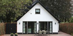 Nieuwbouw huis Laren. Twee onder een kap boerderij uitgebreid met nieuwbouw in stijl van bestaande bouw. Wit gestucte gevels met antraciet kozijnen.