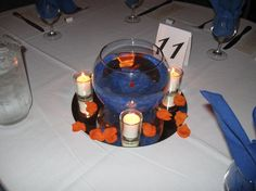 """The bride's favorite color is blue and the groom's favorite color is orange.  These centerpieces were the perfect compromise.  We used real goldfish, blue marbles and orange rose petals.  The bride and groom were able to give the goldfish as """"special"""" favors for their younger guests.  They were a hit!"""