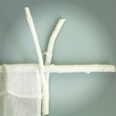 A great DIY on how to use twigs & white paint to create curtain rods & twig decor.Learn how to decorate like a designer!