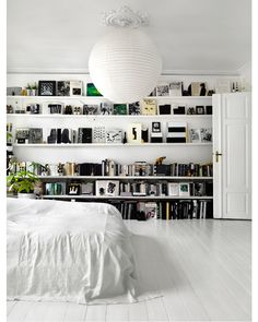 We love the monochromatic wall of shelves in this white-on-white bedroom...