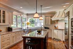 Custom kitchen with windows around sink, pendants above kitchen island - white cabinets - Farinelli Construction