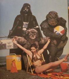 Darth Vader de boa la atrás segurando o pequeno aparelho de som. Leia curtindo a vida e o bicho com uma bola. Star Wars.