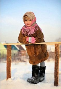 A blonde Russian girl in a traditional shawl, a fur coat and valenki (felted high boots) is standing in the snowy village street.