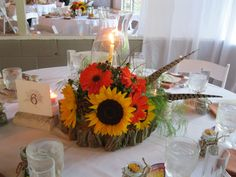 Rustic Centerpiece~ Tapered candle in a glass hurricane surrounded by found acorns & mini pinecones; arrangement of fresh sunflowers, gerber daisies, hypericum berries, pheasant feathers, lotus pods & twigs all sitting on a beautiful cut slab from a fallen tree.