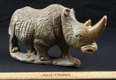 IF YOU LIKE RHINOS, HERE IS A GREAT LOT FOR YOU. HAS A BIT OF DAMAGE ON HIS NOSE. MEASURES 6 IN. X 8 IN. BELIEVED TO BE MADE BY SOME KIND OF STONE.