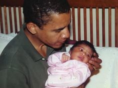 Barack Obama holding his newborn, first-born, Malia.  A touching moment in time.