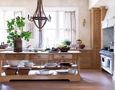 European Country House Kitchen    In a town house in Serenbe, an eco-community in Geogia, a Provençal craftsman built the kitchen's handsome anchor: a weathered French oak island with open storage below. The cabinets, designed by Smith Hanes, are also French oak.