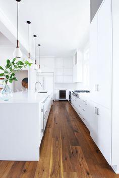 All white kitchen with dark wooden floors.