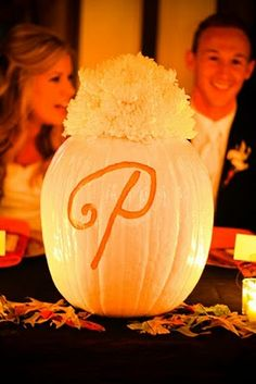 Fall wedding carved monogram pumpkin centerpiece at head table with bride's bouquet placed in top