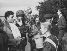 Sergeant Jim Travis of No. 1 Platoon, with his hand in plaster, is drinking a glass of water offered by the Pennings family of the Sinderhoeve. Next to Travis is, also of No. 1 Platoon, 21st Independent Parachute Company, Private Fred Kinsey (with helmet). The para holding the bucket is Sergeant W.N. Hill of the 3rd Parachute Battalion.