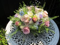 A table arrangement of beautiful pastel flowers in 3 tins finished with moss and tied together, all for a Sunny Country Wedding.