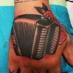 Accordion hand tattoo by Hexa Salmela