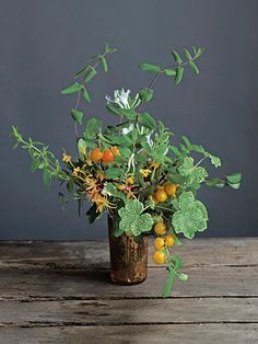 Learn how to make this flower arrangement using honeysuckle, wildplum, and 'Crocodile' geranium leaves