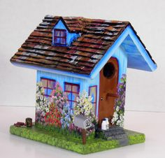 This is a blue handcrafted birdhouse that is hand painted and has an opening on the side for cleaning out. There are little extras on this