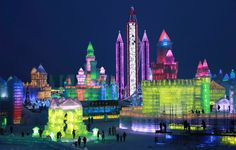 People visit the newly-built ice sculptures illuminated by colored lights during a trial operation of the 16th Annual Harbin Ice and Snow World in Harbin, China, Dec. 22, 2014. The annual Harbin Ice and Snow World will be officially opened on Jan. 5, 2015.