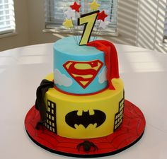 I like the capes and the yellow background with black bat. (little spiderman cake is idea for top) the black stripe at bottom is kinda cool..also like the yellow batman cake with the black buildings/yellow windows..Since I haven't said this anywhere else, I like a royal blue (not light blue) for superman cake (no clouds)
