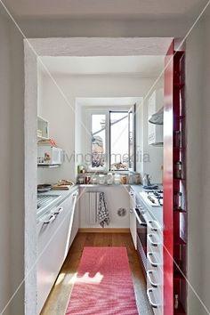 Blick durch offenen Durchgang in schmale, moderne Küche
