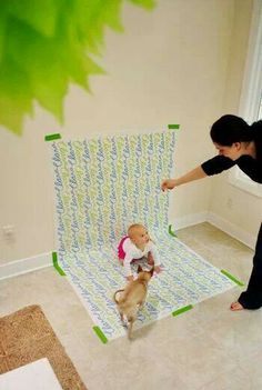 Inexpensive way to take pictures of your child at home.. old wrapping paper, tape and a nice lighted area to shoot