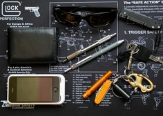 submitted by rick    Fossil trifold wallet with moleskine volant hidden inside.   Maui Jim Stingray Sunglasses.  Sanrenmu 704 with black blade.  Fixed snap shackle/county comm cable keeping essentials together.   mini maglight, Alox Rambler and County Comm delrin $20.00 keeper.  Classic Zebra 701 and Rotring Trio Essential multi pen with stylus.   Iphone 3gs cased in Mophie Juice Air.    Editor's Note: Hey Rick, you have some good ideas in this carry here… It's good to pair your pens…