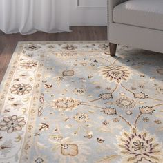 Hand-tufted wool rug with a light blue and ivory floral motif.