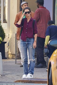Still waiting: The actress paired a plaid shirt with ripped jeans and Adidas sneakers...