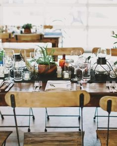 Glass-bottle vases, wooden chairs, and succulent centerpieces lend a cool vibe