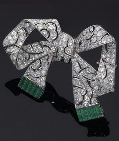 Platinum, gold, diamond and emerald brooch, 1900s. Designed as a ribbon bow, fully pierced and set with diamonds, the ends of the ribbon set with emeralds, mounted in platinum and white gold.