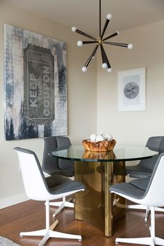 A Sputnik-style light fixture hangs above a vintage dining table and vintage chairs.