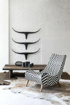 Cette peau de bête en guise de tapis va parfaitement avec les décorations murale tête de buffle, tandis que le fauteuil graphique donne un style mix and match à l'intérieur