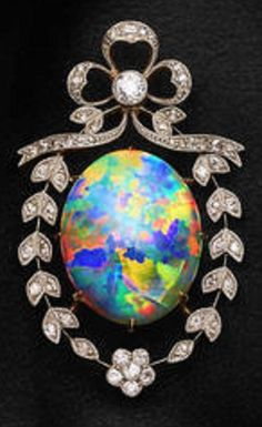 A Belle Epoque opal and diamond brooch, circa 1915. The oval-shaped crystal opal cabochon, measuring approximately 23.0mm x 18.2mm x 5.8mm, displaying exceptional play-of-colour of all spectral colours, set within a ribbon and floral garland surround, mounted throughout with millegrain single-cut diamonds, to the bow surmount, centring an old brilliant-cut diamond collet,  opal weighs approximately 13.80 carats, diamonds approximately 0.70 carat total, mounted in platinum and gold.
