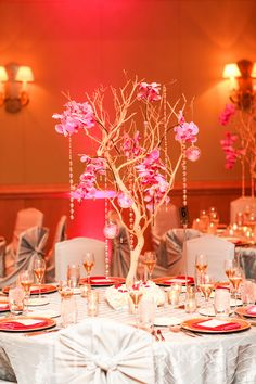 Guest table arrangements of trees with Phalaenopsis orchids and crystal strands