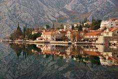 waterlandschap-met-oude-stad-tegen-de-berg-en-een-perfecte-spiegelbeeld