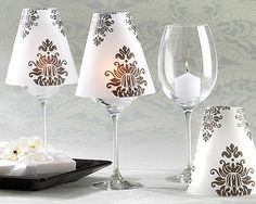 "Damask Vellum Shades (Set of 24) Introducing a new standard in elegant table decor! Imagine the mesmerizing glow our exquisite black-and-white Damask Vellum Shades will create throughout your reception hall. Unforgettable doesn't even begin to describe it! Features and facts-Classic black-and-white damask pattern adorns a translucent, vellum shadeShade fits on standard wine glasses to create a softly glowing table lampAssembled shade measures approximately 4 3/4"" h x 4 1/2"" in diameterWine…"