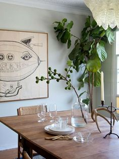 Dining room styling: large scale art, fiddle fig tree, glass bottle with a simple, bold arrangement