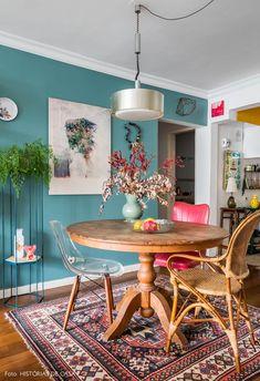 Sala de jantar integrada tem mesa de madeira redonda, cadeira Eames, quadro pendurado na parede azul turquesa, plantas e luminária pendente.