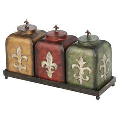 Set of 3 weathered metal jars with fleur-de-lis accents and a complementing tray. Product: 3 Jars and tray Construction Material: Metal Color: Yellow, red and green Features: Fleur de lis design Dimensions: H x W x D (overall) Decorative Objects, Decorative Pillows, Decorative Boxes, Spice Containers, Kitchen Canisters, Kitchen Dishes, Kitchenware, Kitchen Cabinets, Tuscan Decorating