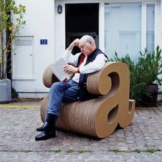 cardboard-large-armchair-cardboard-shelves-letter-a-shape-man-sitting-paved-street Are you looking for ideas for creative and eco-friendly furniture? Then browse through our 60 suggestions for charming cardboard furniture. Cardboard Chair, Cardboard Box Crafts, Cardboard Furniture, Diy Pallet Furniture, Retro Furniture, Furniture Ideas, Furniture Outlet, Furniture Styles, Office Furniture