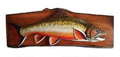 """This carved trout wall plaque will represent the one that got away!Carved wood brook trout on finished wood slab.22"""" x 9"""""""