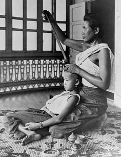 A mother tends to the hair of her daughter in the palace of a high noble, king chula era