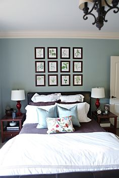This is a nice arrangement of a bed with pictures above it.  www.bowerpowerblog.com