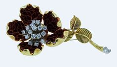 """Van Cleef & Arpels French Enamel En Tremblant  Diamond Brooch. Van Cleef & Arpels 18kt. yellow gold flower brooch with dark reddish enamel petals. The tremblant center is prong set in white gold with 16 round brilliant cut diamonds totaling approximately 1.1 carats. The stem bottom is also set with a round brilliant cut diamond at the base. The diamonds grade Vs clarity G color. The brooch measures 2 1/2"""" signed and numbered. Circa 1980."""